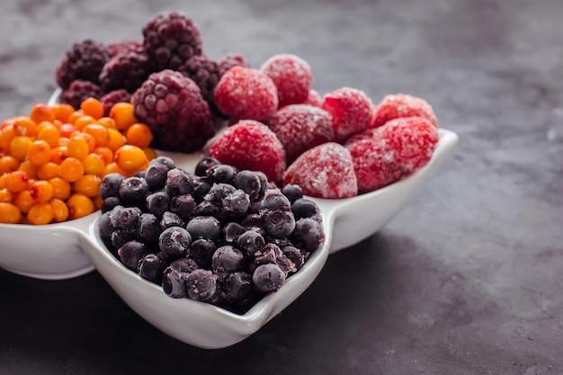 Zamknij si? zamro? one mieszanych owoców i jagód na czarnym stole zdrowe? ywno? ci witaminy deserowe przekąska