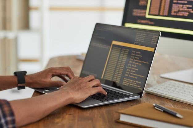 Zamknij się african-american programista komputerowy wpisując na klawiaturze z czarnym i pomarańczowym kodem programowania na ekranie laptopa, kopia przestrzeń