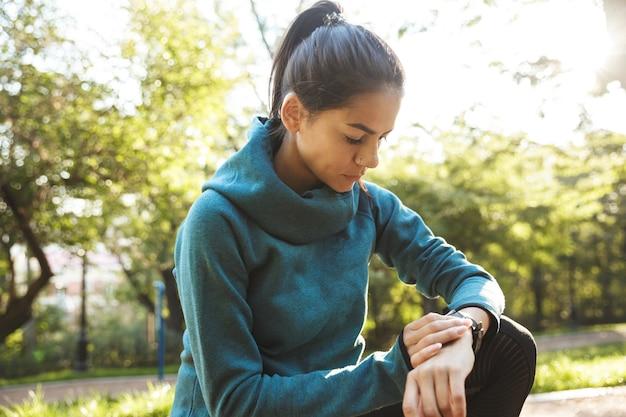Zamknij się atrakcyjna młoda kobieta fitness noszenie odzieży sportowej ćwiczeń na świeżym powietrzu, za pomocą smartwatch