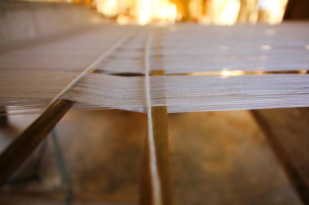 Zamknij się białe przędze na krosnach z drewna, gotowe do produkcji.