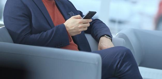Zamknij się. biznesmen korzystający z telefonu komórkowego siedzącego w holu hotelu?