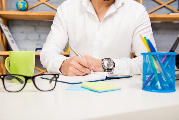 Zamknij się biznesmen pisania notatek w swoim notatniku