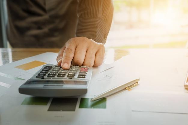 Zamknij się biznesmen przy użyciu kalkulatora i komputera przenośnego do obliczania z finansów papieru, podatku, rachunkowości, koncepcję księgową.