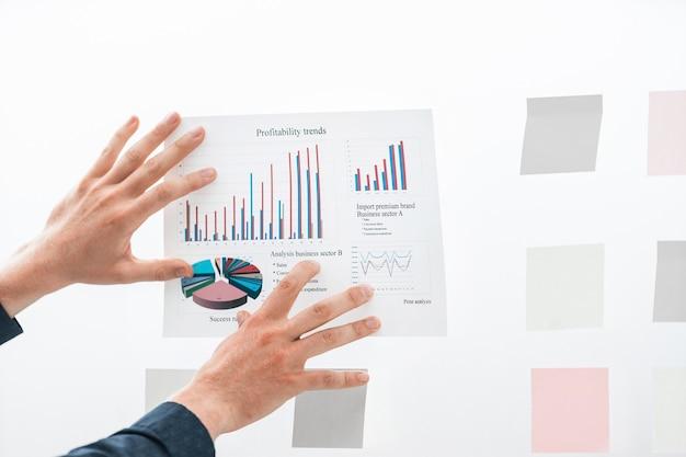 Zamknij się biznesmen trzymanie się szklanej tablicy finansowej wykresu
