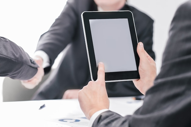 Zamknij się.biznesmen z cyfrowym tabletem na tle uścisku dłoni partnerów biznesowych