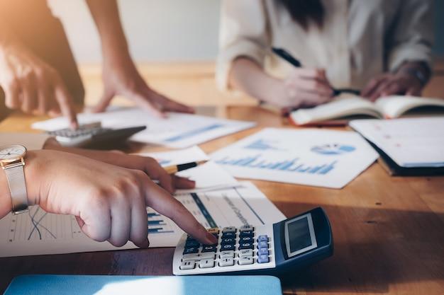 Zamknij się biznesmen za pomocą kalkulatora i laptopa zrobić matematyki finansów na drewnianym biurku