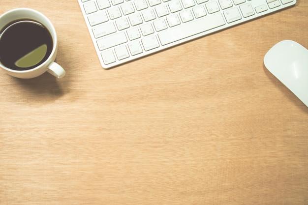 Zamknij się, brązowe drewniane biurko z komputerem i kawą w górnej części obrazu.