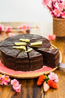 Zamknij się ciasto czekoladowe z cięcia kawałek i ostrze na tacy