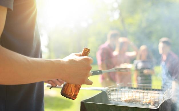 Zamknij się człowiek co grilla i trzymając butelkę piwa.