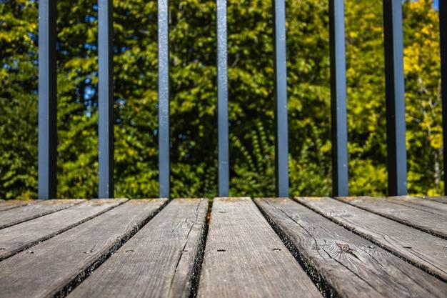 Zamknij się drewniany chodnik z metalowymi balustradami tła.