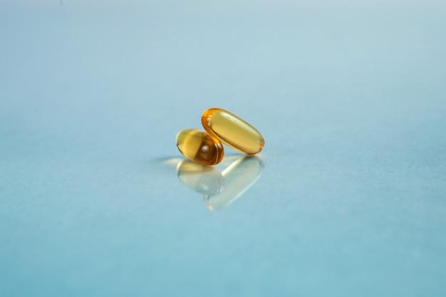 Zamknij się dwie kapsułki omega-3 na niebieskim tle z odbiciem. pojęcie opieki zdrowotnej.