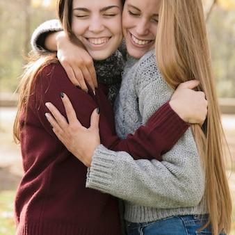 Zamknij się dwie przytulanie młodych kobiet w parku