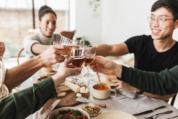 Zamknij się grupa międzynarodowych przyjaciół trzymając w rękach kieliszki wina