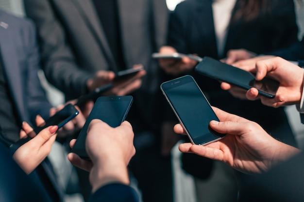Zamknij się. grupa pracowników spoglądających na ekrany swoich smartfonów. ludzie i technologia