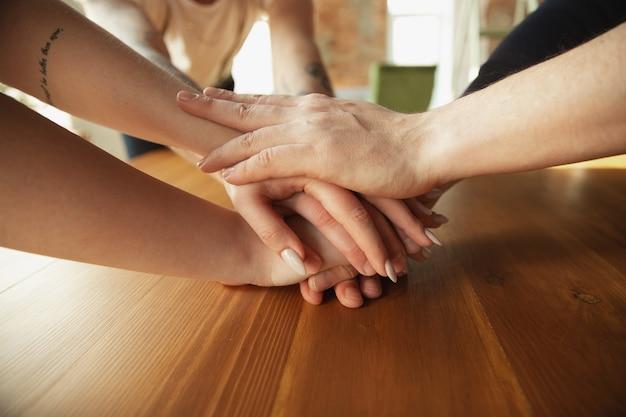 Zamknij się kaukaski męskich i żeńskich rąk, zakrywając się nawzajem, drżenie. pojęcie biznesu, finansów, pracy. miejsce na reklamę. edukacja, komunikacja i freelancer. budowanie zespołu, wsparcie.