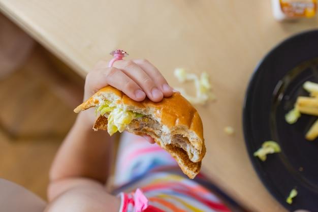 Zamknij się kobiet ręce trzymając pyszny burger boczek.