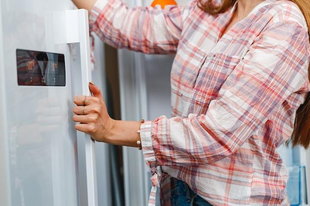 Zamknij się kobieta, otwierając drzwi lodówki