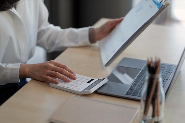 Zamknij się kobieta pracująca o finanse z kalkulatorem w jej biurze, aby obliczyć wydatki, koncepcja rachunkowości narzeczonej.