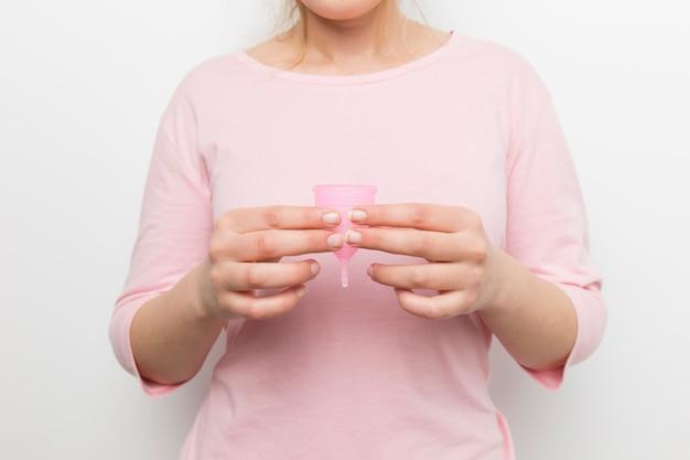 Zamknij się kobieta trzyma kubek menstruacyjny