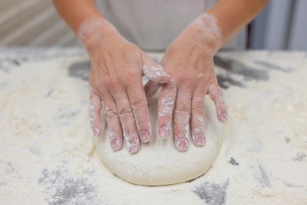 Zamknij się kobieta wyrabiania ciasta do pizzy.