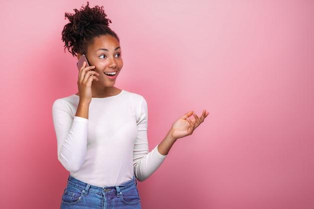 Zamknij się kobieta youngmulatto rozmawia przez telefon komórkowy z szczęśliwym wyrazem twarzy.