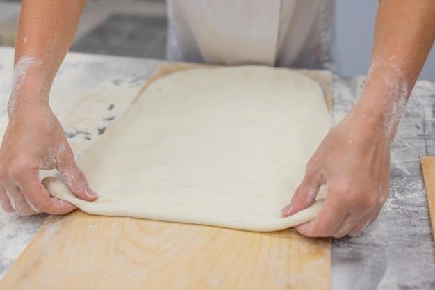 Zamknij się kobiety wyrabiania ciasta do pizzy.