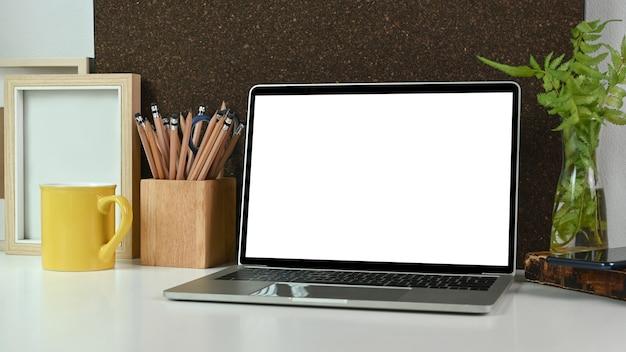 Zamknij się komputer laptop z pustego ekranu, uchwyt na ołówek, filiżankę kawy i roślina doniczkowa na białym stole.