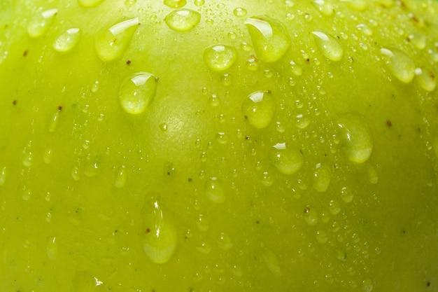 Zamknij się krople wody na świeże zielone jabłko, mała głębia ostrości.