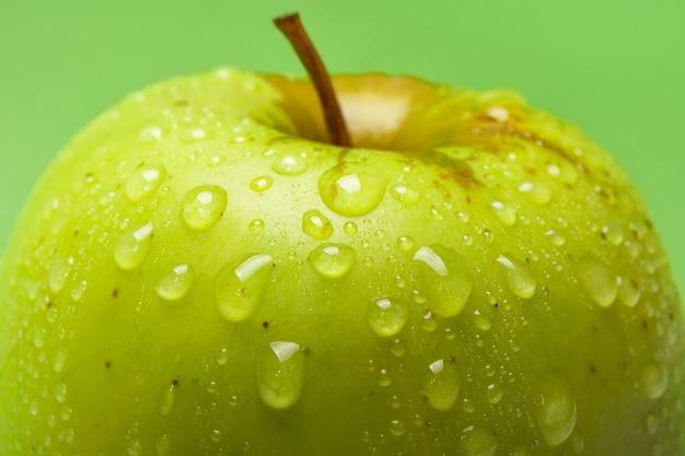 Zamknij się krople wody na świeże zielone jabłko na zielonym tle, mała głębia ostrości.