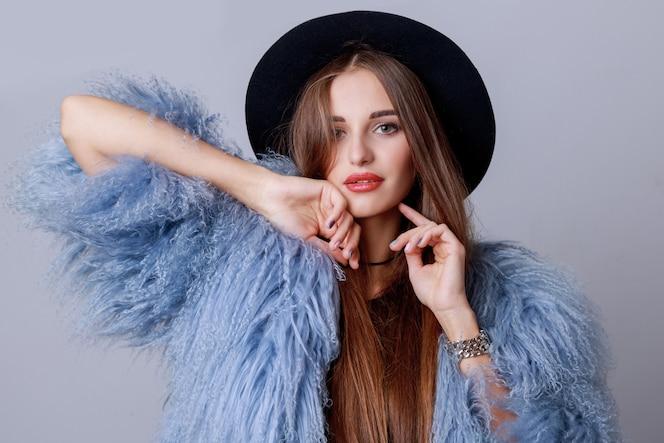 Zamknij się kryty moda portret całkiem młody model w stylowy zimowy puszysty płaszcz i czarny kapelusz pozowanie. wieczorny jasny makijaż.