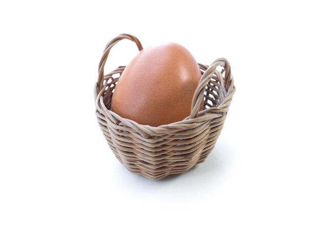 Zamknij się kurze jajo w koszu na białym tle