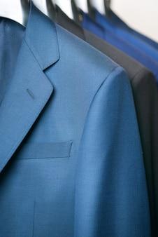 Zamknij się luksusowy rząd garnitur dżentelmenów, wiszące w szafie.
