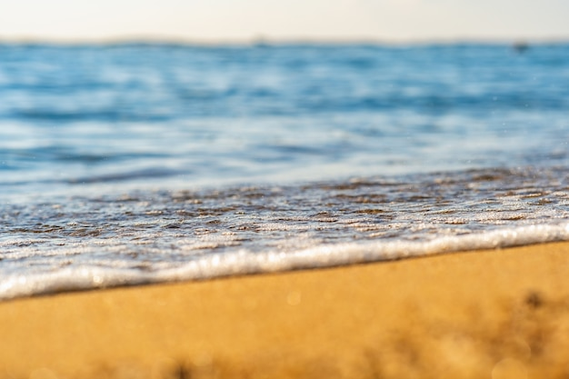 Zamknij się małe fale morskie z czystą, błękitną wodą na żółtej piaszczystej plaży na letnim słonecznym brzegu.
