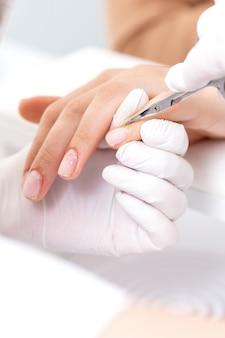 Zamknij się manikiurzystka za pomocą nożyczek do manicure, aby usunąć naskórek kobiecych paznokci w salonie manicure