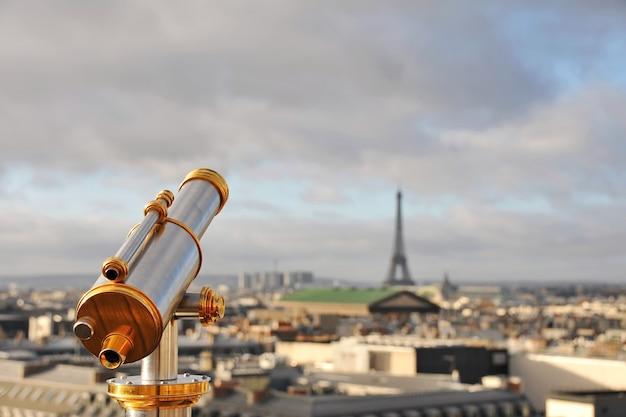 Zamknij się metalowy teleskop z widokiem na panoramę paryża we francji
