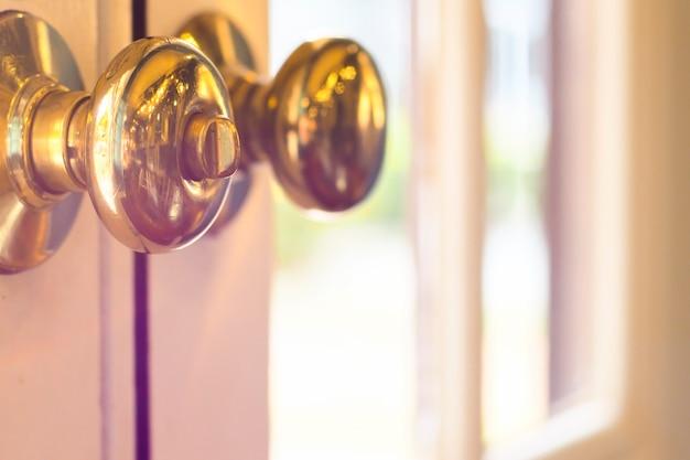 Zamknij się metalowy uchwyt na stare drewniane drzwi, złote klamki. bliska metalowy uchwyt na stare drewniane drzwi, złote klamki.