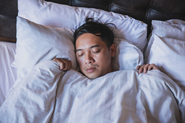 Zamknij się mężczyzna śpiący na łóżku z białym kocem