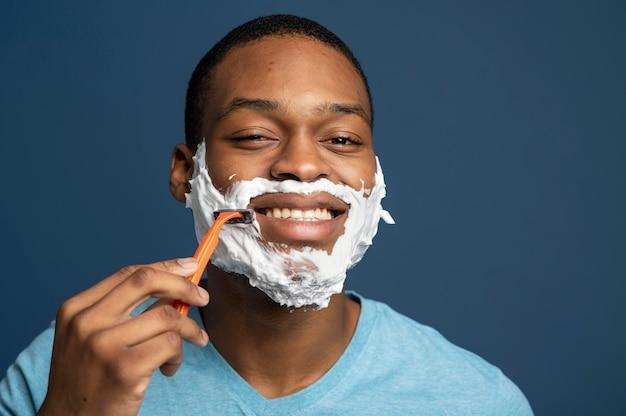 Zamknij się mężczyzna używający brzytwy do golenia