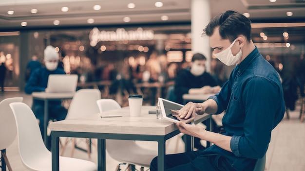 Zamknij się. mężczyzna w masce ochronnej wycierającej ekran cyfrowego tabletu środkiem antyseptycznym.