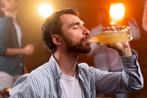 Zamknij się mężczyzna z drinkiem w klubie