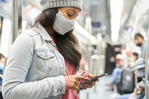 Zamknij się młoda kobieta afroamerykanów sprawdzanie telefonu w samochodzie metra.
