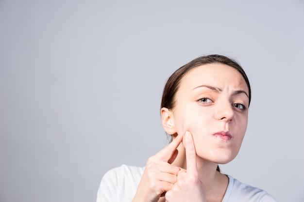 Zamknij się młoda kobieta nakłuwania zaskórników na jej policzku, patrząc na kamery poważnie. uchwycone w studio z szarym tłem.
