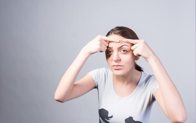 Zamknij się młoda kobieta nakłuwanie pryszcz na czole, patrząc na kamery poważnie. zrobione w studio z szarym tłem