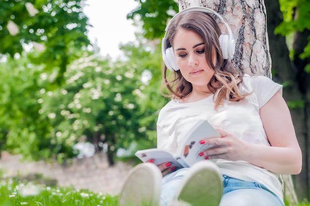 Zamknij się młoda kobieta relaksu czytania i słuchania muzyki na słuchawkach na zewnątrz w dzień wiosny. pojęcie wolnościowe z pięknym kobietą relaksu na zewnątrz z muzyką, książek i kawy
