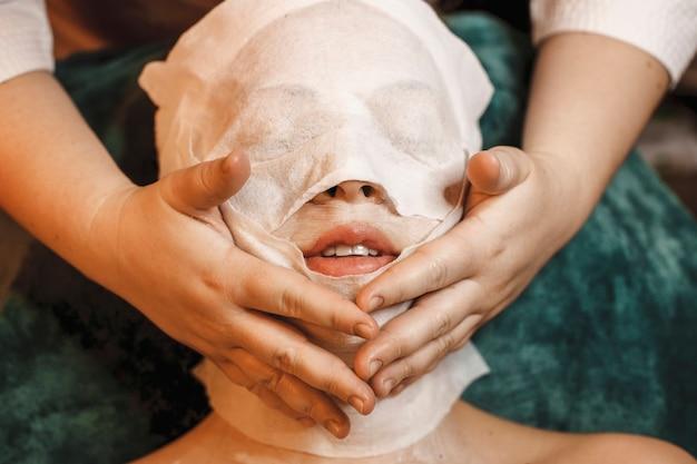 Zamknij się młoda kobieta robi zabiegi pielęgnacyjne skóry twarzy w centrum odnowy biologicznej spa.