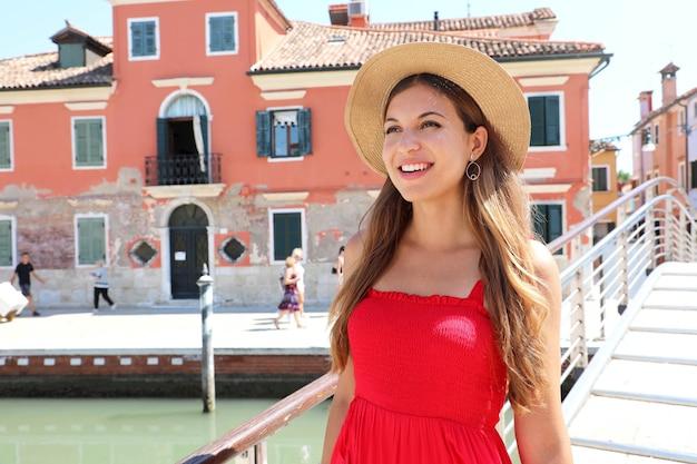 Zamknij się młoda kobieta w czerwonej sukience spaceru na moście w miejscowości burano, wenecja, włochy