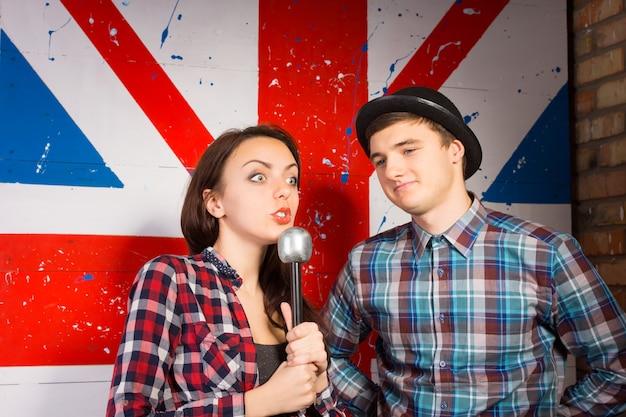 Zamknij się młoda kobieta z mikrofonem, pokazując wyraz szeroko otwarte oczy, wywiad młody mężczyzna gość w modnym stroju z przodu ogromny druk flagi brytyjskiej.