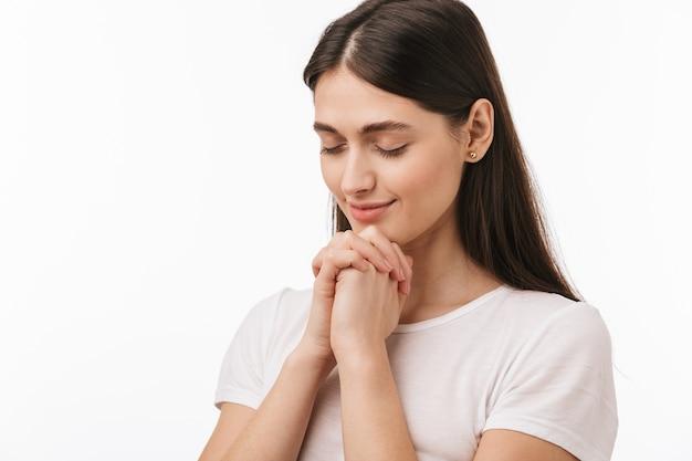 Zamknij się młoda piękna kobieta na białym tle, modląc się