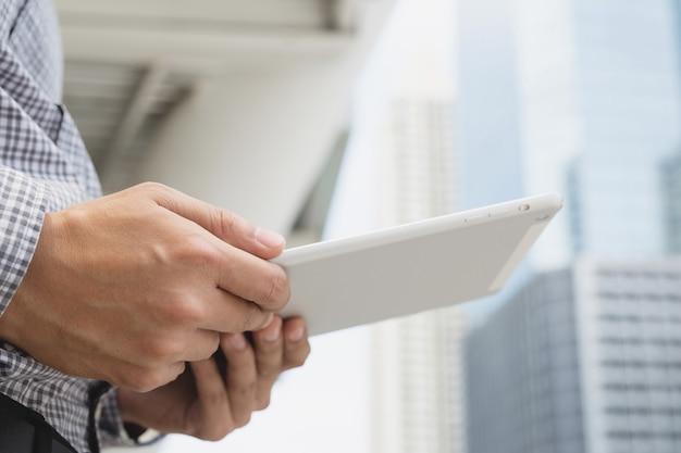 Zamknij się młody azjatycki człowiek za pomocą tabletu. lub biznesmen kontakt z klientem
