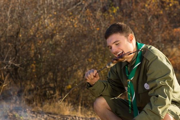 Zamknij się młody biały mężczyzna scout jedzenie gorącej kiełbasy z grilla na terenie obozu.